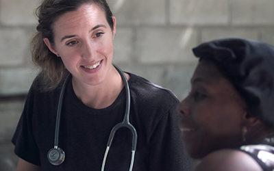En kvinna med stetoskop runt halsen pratar med en annan kvinna